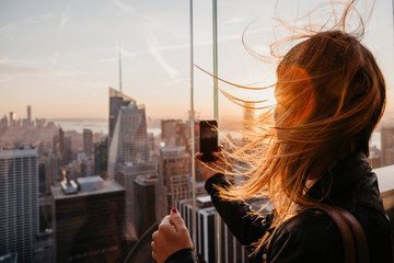 USA, New York, New York City, woman taking a photo at sunrise