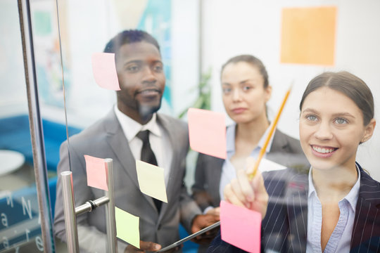 Multi-ethnic group of business people planning startup project placing sticky notes on glass wall, copy space