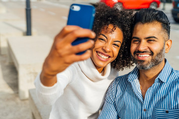 Happy couple taking a selfie outdoors