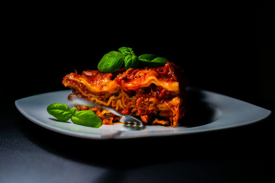 Slice of traditional italian lasagne with vegetables, minced meat and cheese and basil decoration. On a white dish and black background. The fork inserted into lasagna