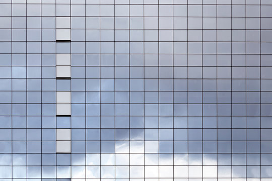 Surface of glass building with the reflection of clouds