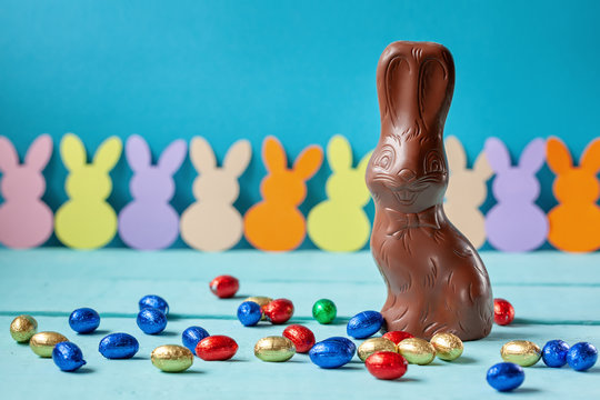 Chocolate easter bunny with chocolate eggs on blue background.