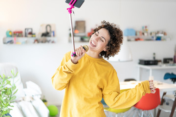 Carefree woman at home singing into microphone attached to a selfie stick