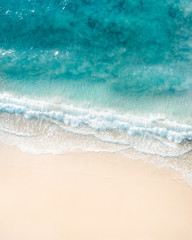 Beautiful aerial shot of a beach with nice sand, blue turquoise water. Top shot of a beach scene with a drone