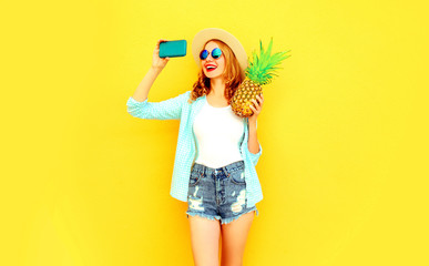 happy smiling woman with pineapple taking selfie picture by phone in summer round hat, sunglasses, shorts on colorful yellow background
