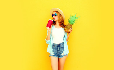 pretty young woman drinking juice, holding pineapple in summer straw hat, sunglasses, shorts on colorful yellow background
