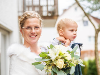 Portrait of happy bride with little girl and bridal bouquet