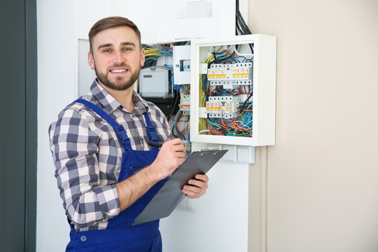 Male electrician with clipboard near fuse board indoors, space for text