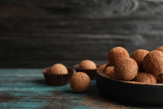 Plate of chocolate truffles on wooden table, space for text