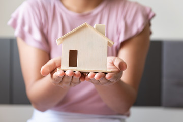 Close-Up Woman Hands is Holding House Model, Business Property and Investment Real Estate Concept, Saving Money, Loan for Housing.