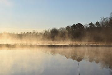 Steam fog rises over ponds on a cold spring morning in Mississippi