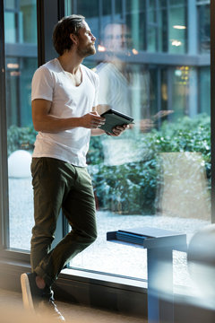 Pensive business man with tablet looking outside of large window front in modern office building