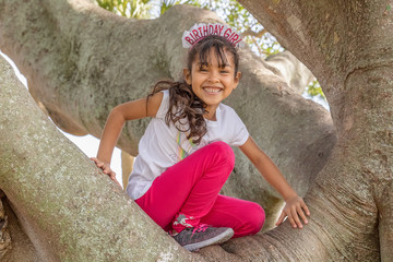 A happy birthday, the girl smiles from the top of the tree. She is so excited to reach the top of a large banyan tree on her birthday.