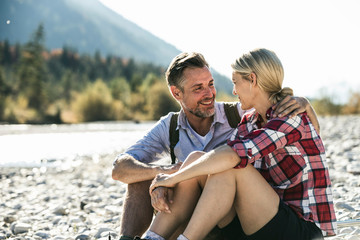 Austria, Alps, happy couple on a hiking trip having a break at a brook