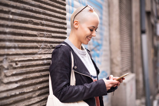 Young modern bald woman talking on her cell phone, enjoying a beautiful day outside in an urban city area