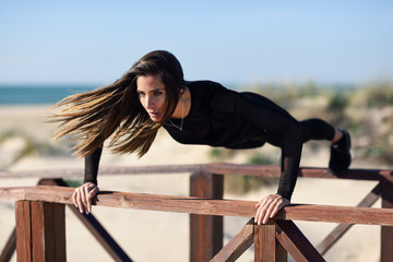 Sportive woman doing push-ups on railing of a wooden bridge