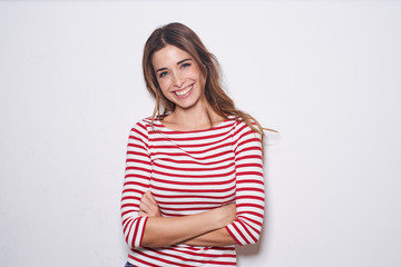 Portrait of laughing young woman wearing red-white striped shirt against white background
