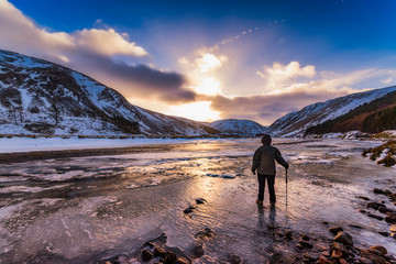 United Kingdom, Scotland, Highlands, female hiker standing at icy riverside