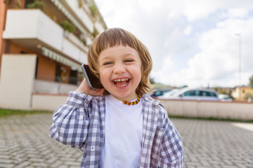 Portrait of laughing toddler boy on cell phone outdoors