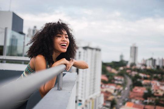 Panama, Panama City, portrait of happy young woman on balcony