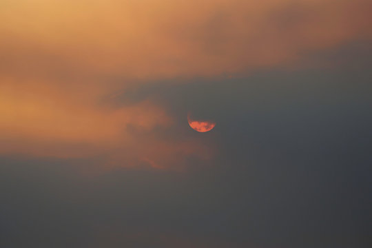 An orange sun peering through the clouds that are white and grey with an orange sky from a bush fire haze.