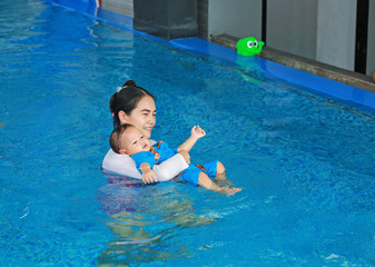 Young Asian mom teaching baby boy in swimming pool