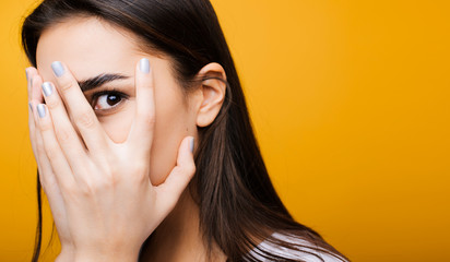Close up portrait of a cute young european girl hiding face with her hand while looking at camera through fingers in front of a yellow studio background.