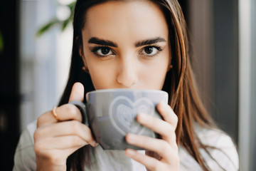 Close up portrait of a attractive brunette drinking coffee while looking at camera sitting in a coffee shop near a window.