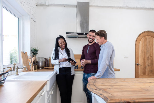 Female real estate agent showing gay couple around new house