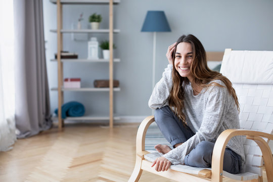 Home lifestyle woman relaxing on cozy chair in living room.