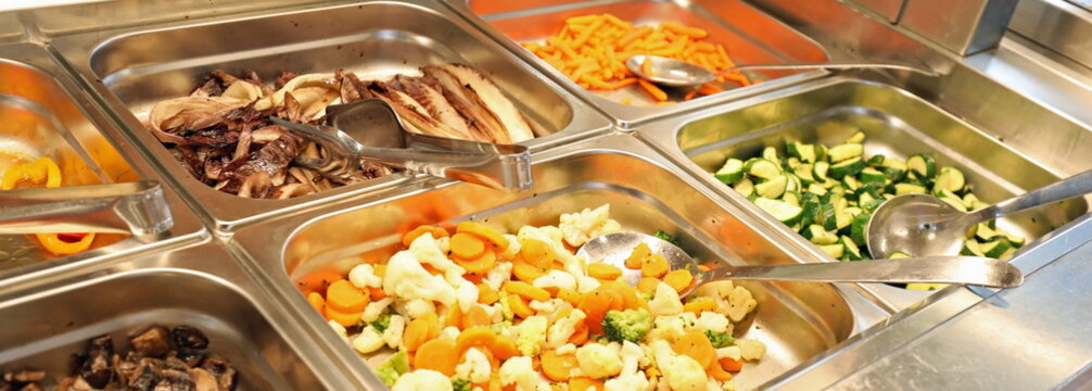 steel trays with plenty of vegetables cooked and raw in the cafe
