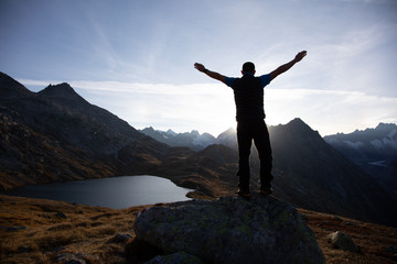 Hiker is standing on a rock with raised hands and enjoying sunrise in the Alps in Switzerland