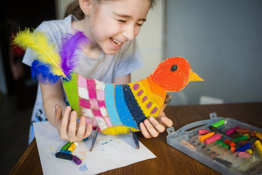 craft with kids. bright bird, cut from cardboard and painted with wax crayons,in the hands of a child. process of creating