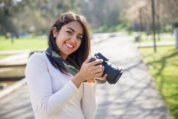 Positive successful photographer enjoying photo-shooting