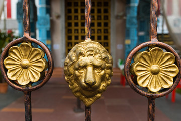 Golden lion head on metal fence decorating at Sri veeramakaliamman temple, Singapore.