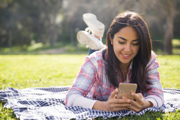 Smiling focused girl typing message on smartphone