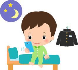 就寝前にスマートフォンを使う男の子
