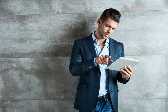 Confident businessman using tablet at office