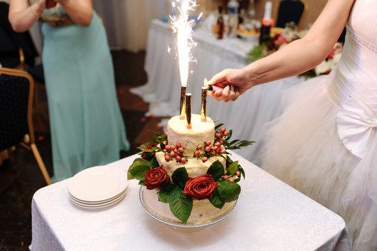 Bride lights fireworks on wedding cake