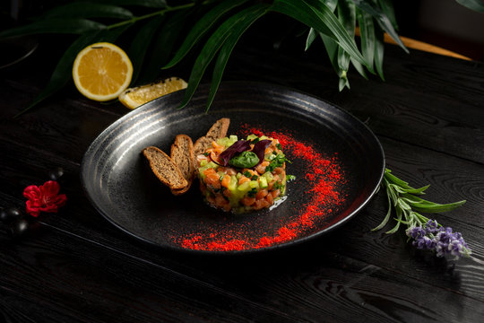 salmon tar-tar on a black plate on a wooden background