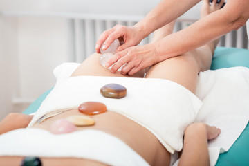 Woman receiving thigh massage with stone