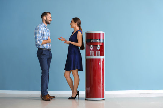Man and woman near water cooler against color wall