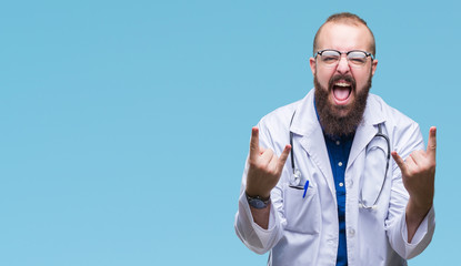 Young caucasian doctor man wearing medical white coat over isolated background shouting with crazy expression doing rock symbol with hands up. Music star. Heavy concept.