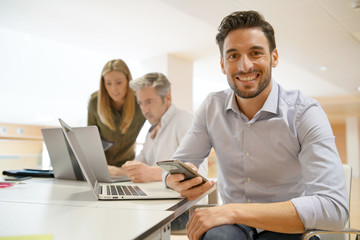 Startup team member smiling at camera in office