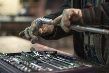 Close up wrench set and worker hands