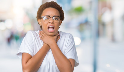 Beautiful young african american woman wearing glasses over isolated background shouting and suffocate because painful strangle. Health problem. Asphyxiate and suicide concept.