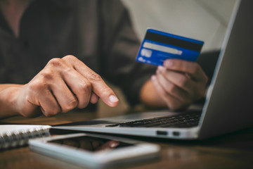 Businessman holding credit card and typing on laptop for online shopping and payment makes a purchase on the Internet, Online payment, Business financial and technology