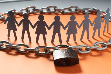 Human paper figures in front of metal chain and padlock on a red surface. Freedom, independence, human rights concept.