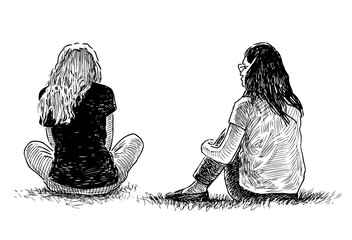 Two teenage girls sitting on the grass in a city park