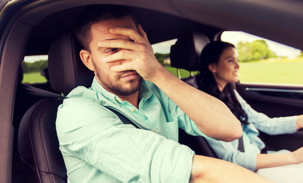 leisure, road trip, travel and people concept - woman learning to drive car and scared man covering face with his palm